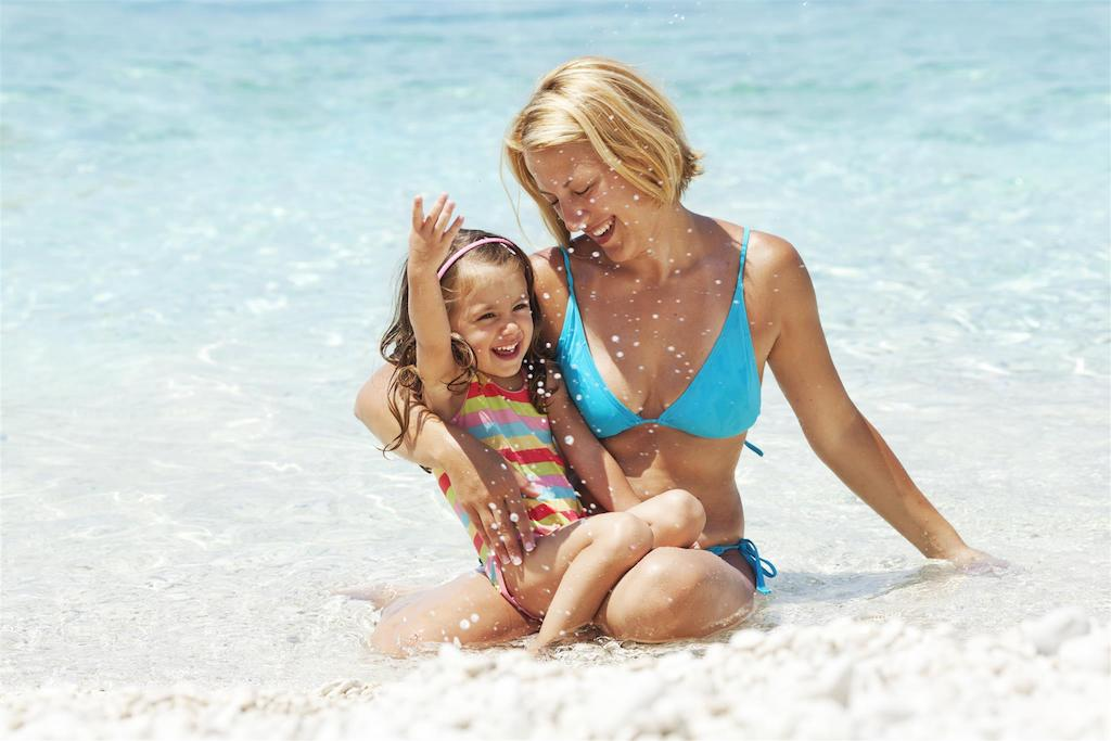 Mother with toned body after mommy makeover, enjoying beach with daughter