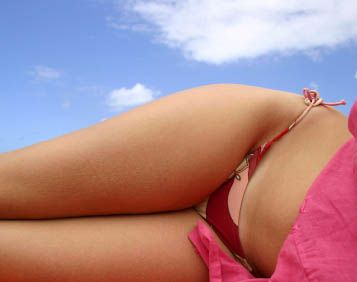 A woman in a bikini after tickle lipo body sculpting