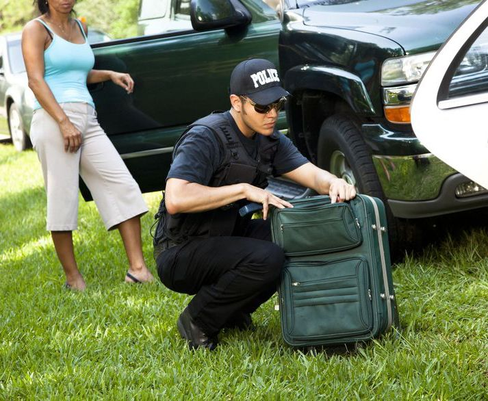 An officer looks for drugs in a woman's suit case