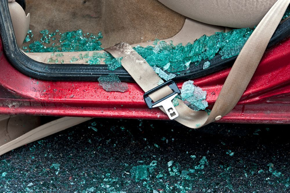 A car seat littered with broken glass