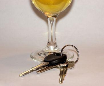 A glass of white wine aside a set of car keys.
