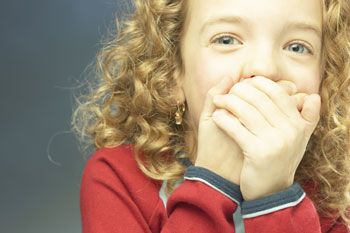 Laughing, young girl with curly, blond hair holding hands over mouth