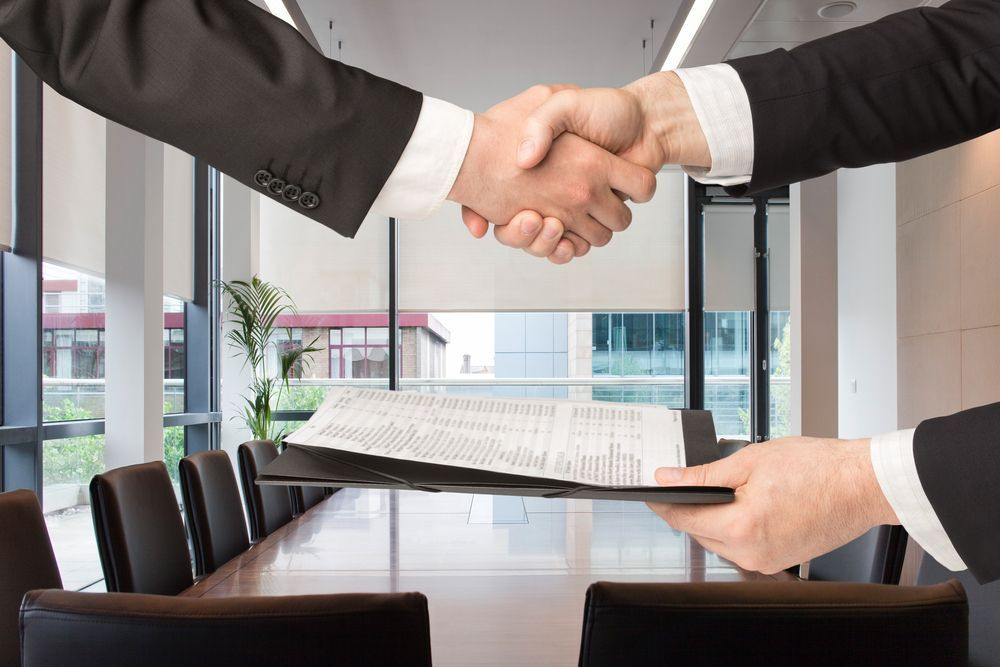 A close up of two people shaking hands after signing a contract