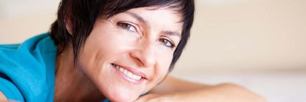 Smiling dark-haired woman with head resting on arm