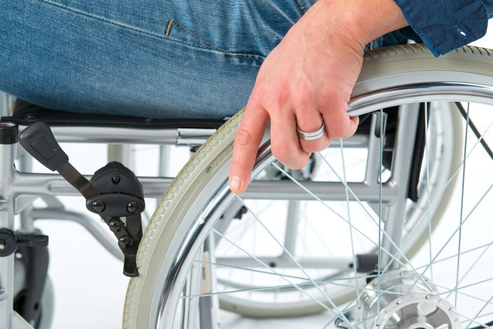 A close up of a man's hand resting on his wheel chair tire