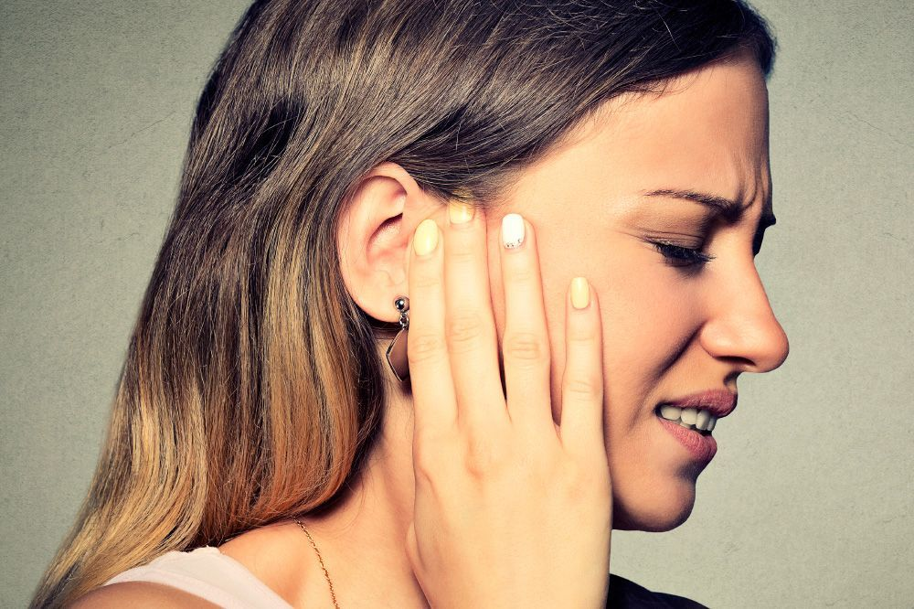 A young woman clutches her ear in pain and fear struggling to hear