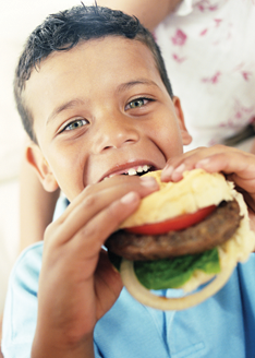 Happy boy eating a hamburger.