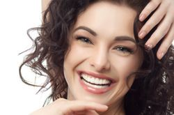 Smiling woman with curly brown hair holding hands around face