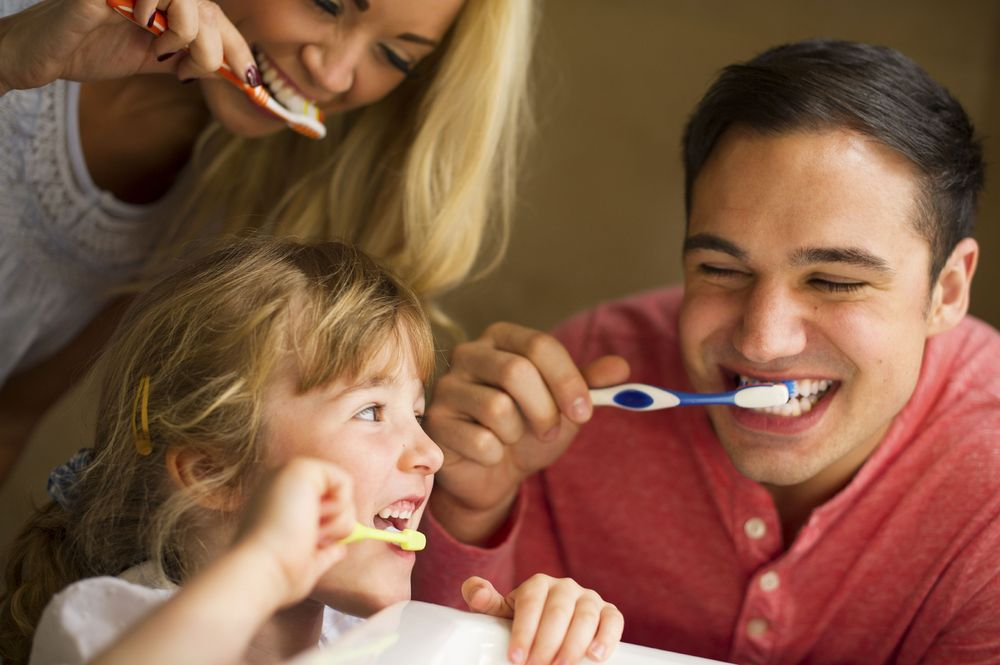 Photo of parents brushing their teeth with a young child