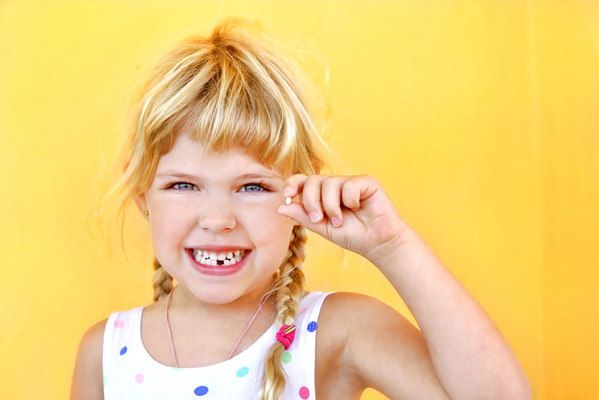 Smiling young girl holding extracted tooth