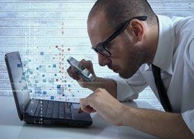 Man looking at laptop through magnifying glass