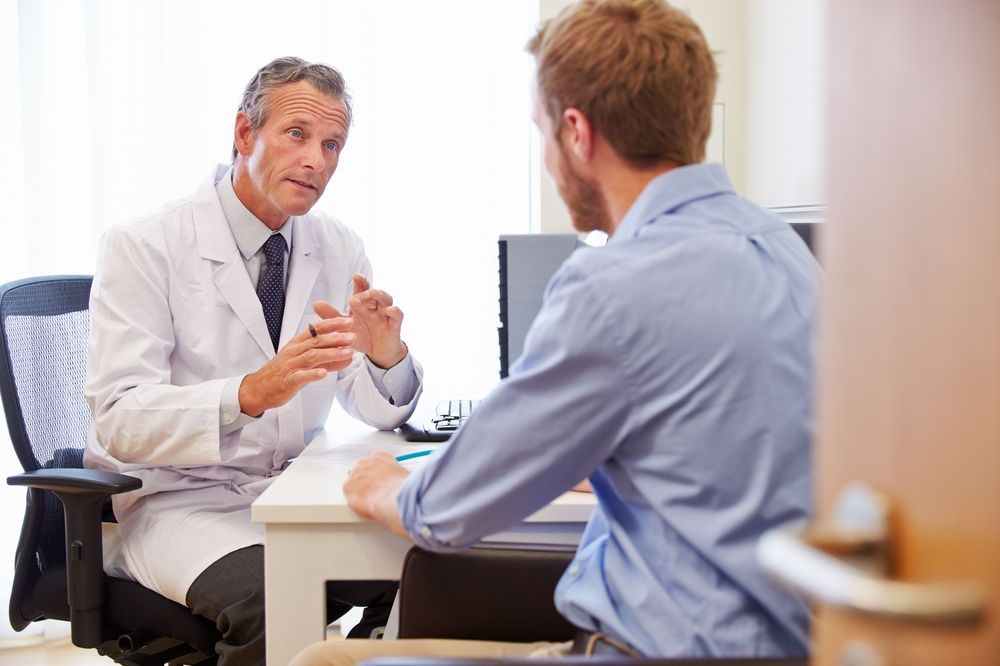 A doctor discusses risk of a procedure with a patient in his office