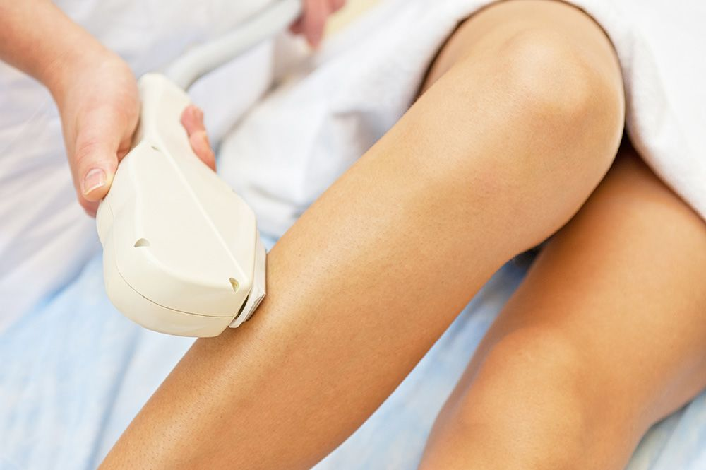 A close up of a woman's legs being treated with a laser hair removal device