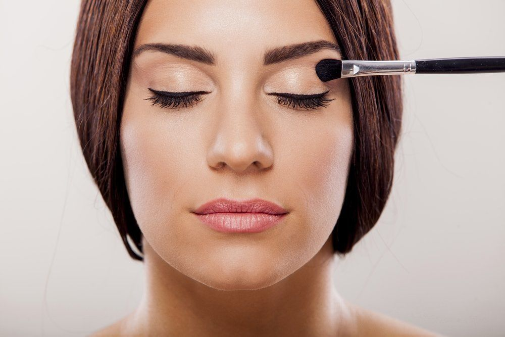 Woman with closed eyes and makeup brush applying eyeshadow
