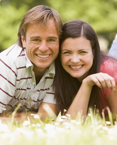 Smiling couple lying on stomachs in grass