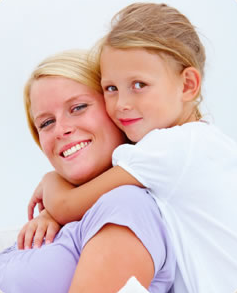 Smiling blond woman piggybacking small girl