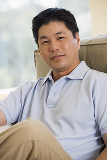 A man sitting sitting on a beige couch wearing a blue collared shirt.