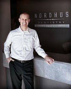 Dr. Byron J. Nordhus standing in front of his dental logo.