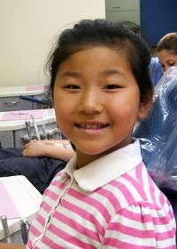 An adorable small girl wearing a pink-and-white striped shirt, sitting in a dentist's office.
