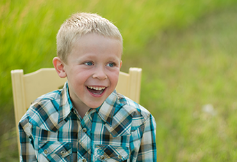 Little boy smiling while sitting in a chair
