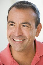 Smiling man with gray hair and collared peach shirt