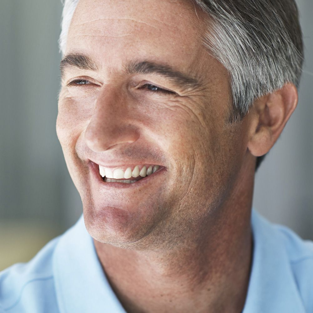 A middle-aged man smiles after a full mouth reconstruction