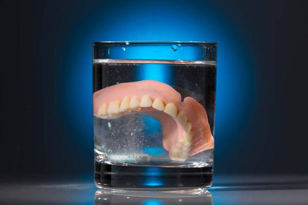 Denture soaking in glass of water