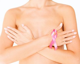 Woman holding arms crossed over naked chest with breast cancer awareness ribbon on wrist