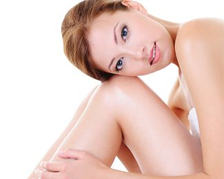 Attractive woman in bath towel resting cheek on bent knees
