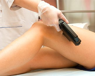 Woman undergoing professional hair removal on her legs