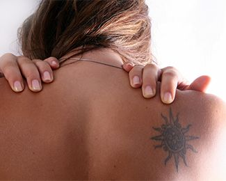 Woman showing unattractive tattoo on her shoulder blade