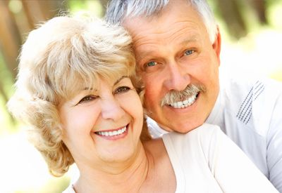 An older couple, both with complete and beautiful smiles