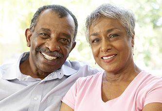 An older couple posing and smiling outside