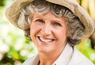 An older woman outdoors in a hat