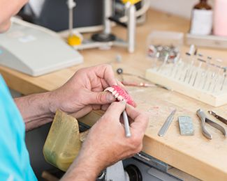 A lab technician crafting a dental restoration