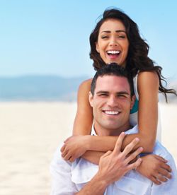 Laughing couple on sand with man boosting woman up on his back