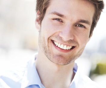 A young man in a collared shirt smiling