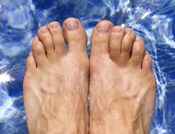 Ariel view of mans feet as he is about to dive into a clear blue swimming pool