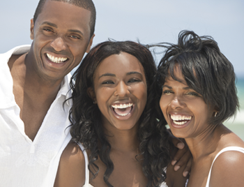 A happy smiling family of father, mother, and daughter at the beach in the summer