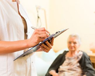Woman taking notes on clipboard with blurred nursing home patient in background