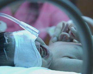 Crying newborn with eye mask lying in incubator