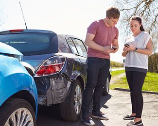 Man and woman exchanging contact information at the scene of a car accident