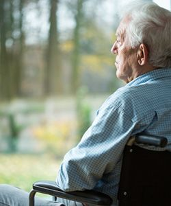 A senior man sits at the window at his nursing home