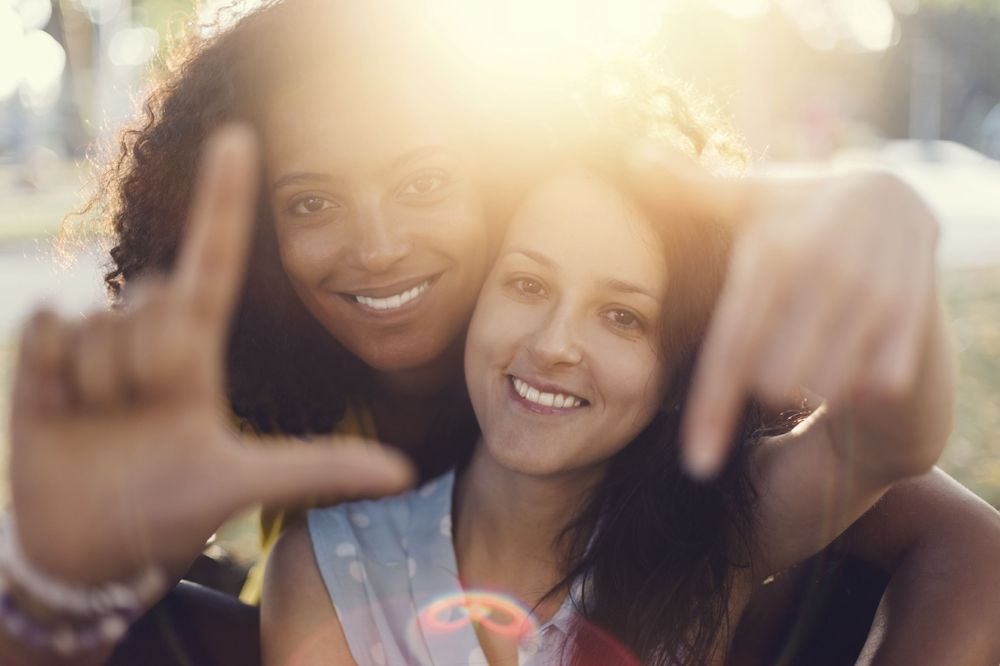 Two young women smile together happily