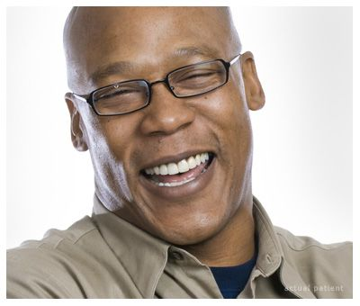 A bald man laughing happily with his eyes nearly closed.