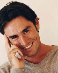 Laughing man with thick, dark hair holding hand to cheek