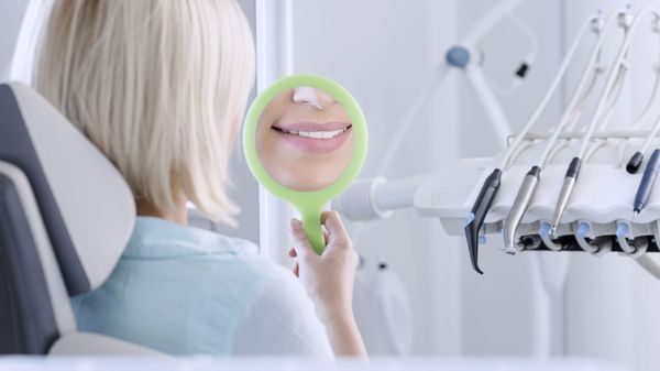 A woman smiling into a handheld mirror.