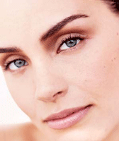 A closeup view of a beautiful woman with dark eyebrows and light eyes.