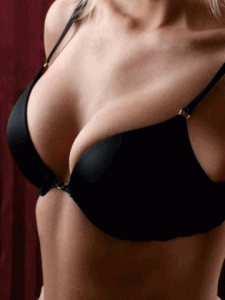 A woman with large breasts inside of a black bra.