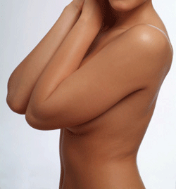 A side view of a topless woman holding her elbows over her breasts.